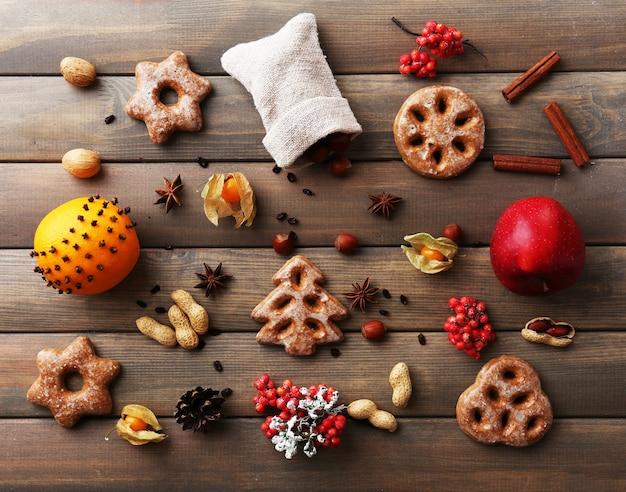 木製の背景に果物やスパイスとクッキー