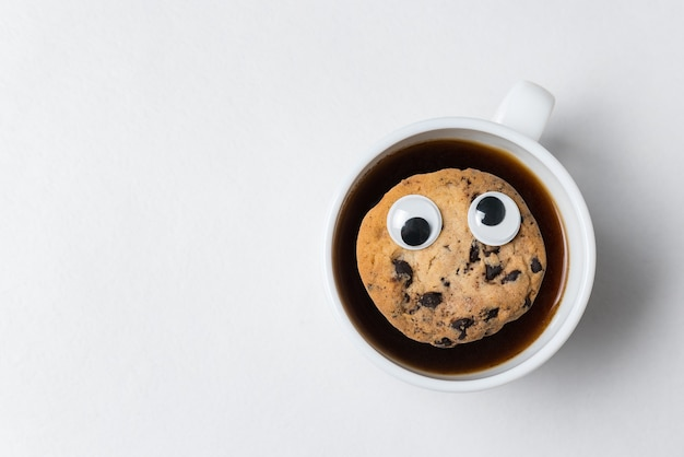 Cookies with googly eyes floating in cup of tea. coffee cup with cookies on white background, top view