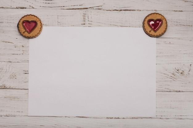 Biscotti con un cuore negli angoli di una carta bianca