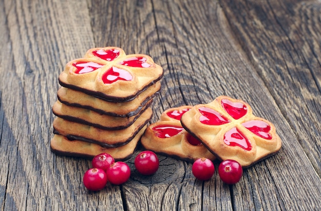 Cookies with jam and cranberry on wooden table