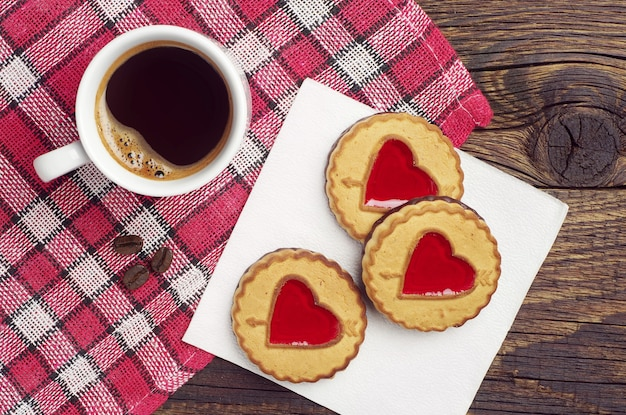 Cookies with jam in shape of hearts and cup of black coffee on red tablecloth, top view