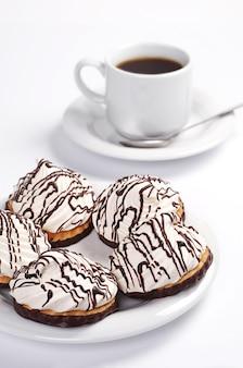 Печенье с шоколадным безе и чашкой кофе на белом фоне