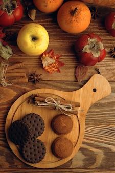 テーブルの上のミルクとクッキー。カボチャとテーブルの上のリンゴと木の板のクッキー。