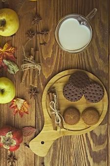 テーブルの上のミルクとクッキー。カボチャと木製のテーブルの上のカボチャクッキー