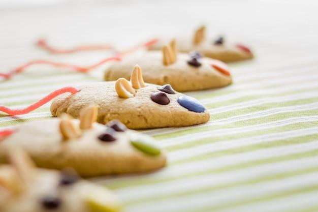 녹색 줄무늬 식탁보 위에 쥐 모양과 붉은 감초 꼬리가 있는 쿠키