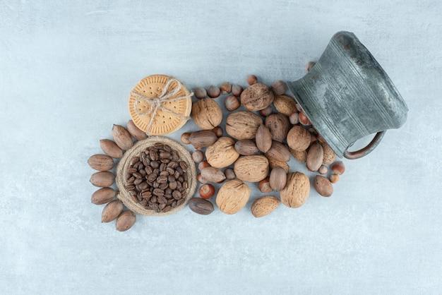 흰색 바탕에 견과류와 고대 컵이 있는 쿠키. 고품질 사진