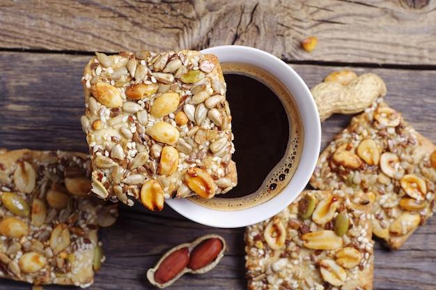 Печенье с орехами, семенами и кофейной чашкой на старом деревянном столе, вид сверху