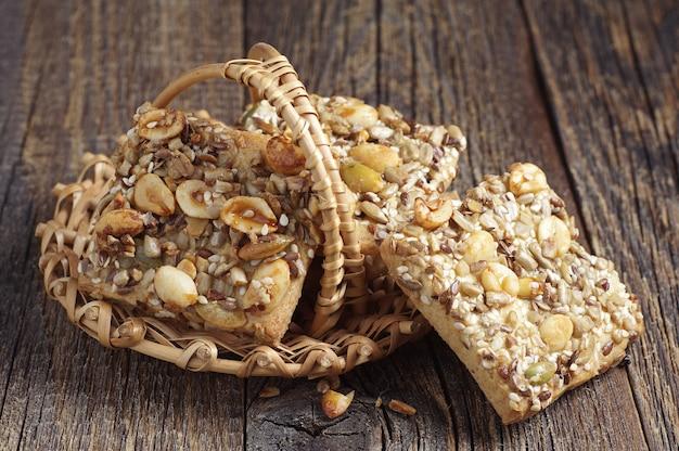 Печенье с орехами, кунжутом и семечками в грелке на старом деревянном фоне
