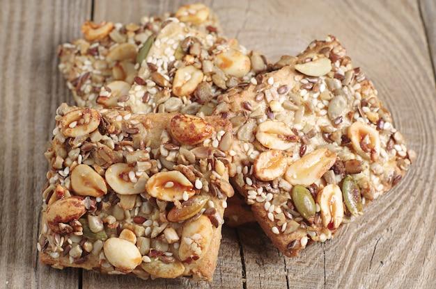 Печенье с орехами, кунжутом и семенами подсолнечника на старом деревянном столе. макро фото