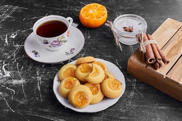 Biscotti con marmellata di arance serviti con una tazza di tè.
