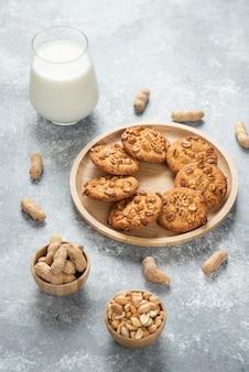 大理石のテーブルに有機ピーナッツとミルクのグラスが入ったクッキー。