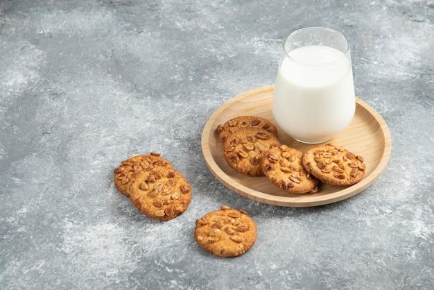 나무 접시에 유기농 땅콩과 우유 한 잔을 넣은 쿠키.