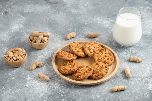 Biscotti con arachidi biologiche e bicchiere di latte sul tavolo di marmo.