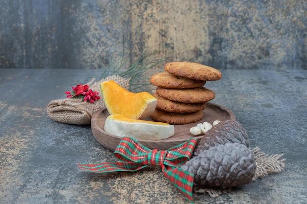 Biscotti con pigne e due fette di zucca su piatto di legno.