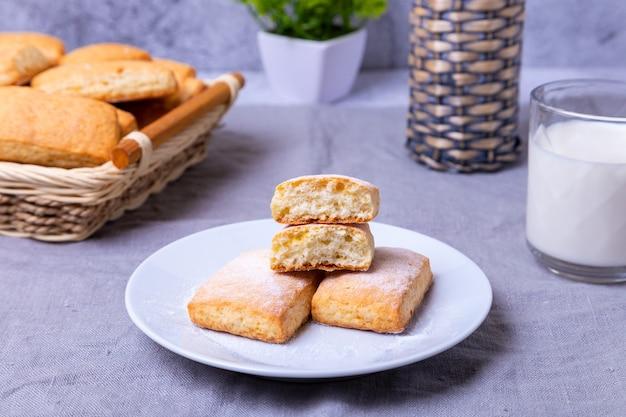Печенье с сахарной пудрой на белой тарелке. на заднем плане корзина с печеньем и чашка молока. крупный план.