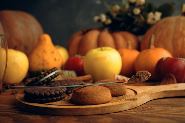 Cookies  with pumpkins and apples on the table.
