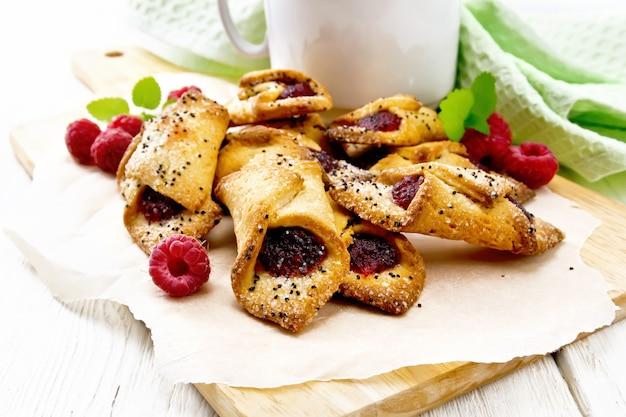 Печенье с малиновым вареньем, ягодами и мятой на пергаменте на доске