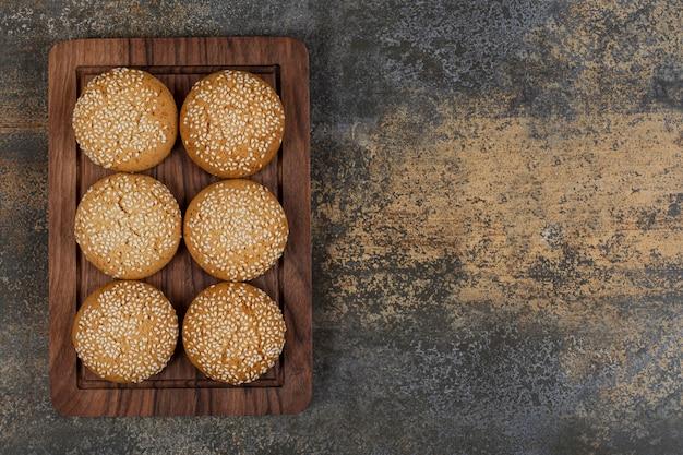 Печенье с кунжутом на деревянной тарелке.