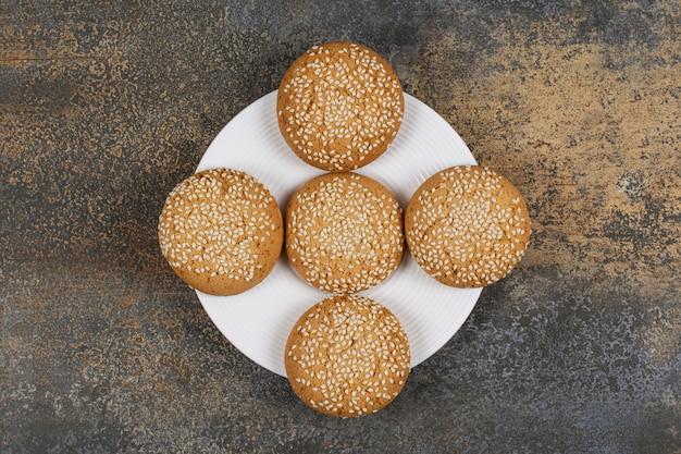 Печенье с кунжутом на белой тарелке.