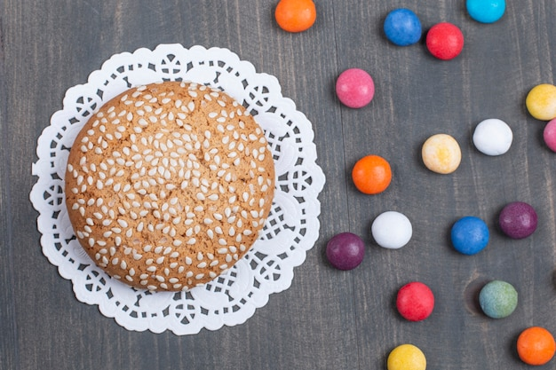 Biscotti con semi di sesamo su superficie di legno con cioccolatini