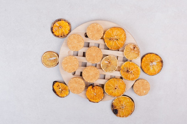 Cookies with slices of orange on wooden plate