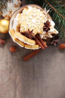 木製のテーブルに、スパイスとクリスマスの装飾が施されたクッキー