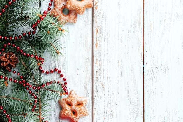 色の木製の背景にクリスマスツリーの小枝とクッキー