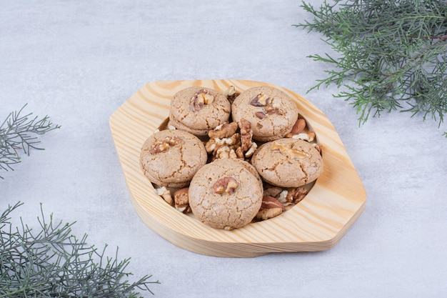 Cookies with walnut kernels on wooden plate.