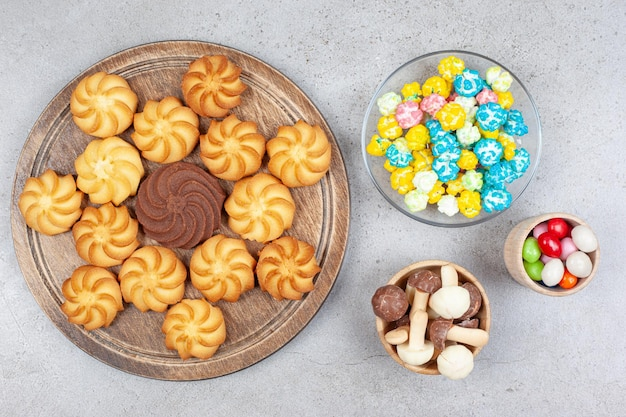 Cookies on wooden board next to bowls of candies and mushroom chocolate on marble surface.