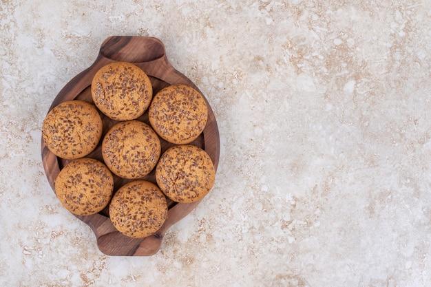 Biscotti su un piatto di legno, sul tavolo di marmo.