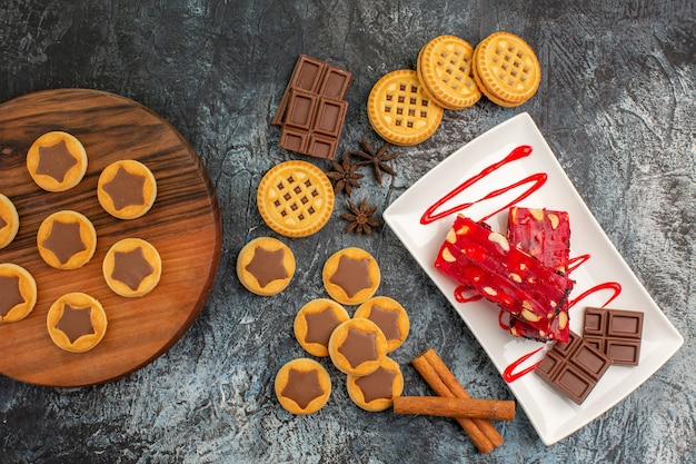 Cookies on wooden platter and a plate of chocolate on grey