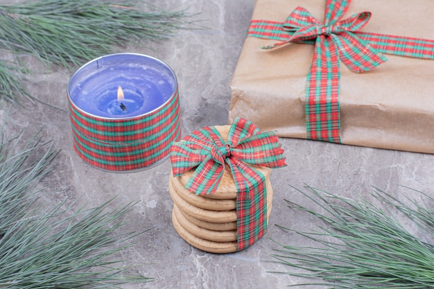 Cookies in a wrap with a blue flaming candle and a gift box around.