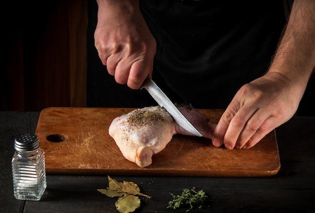 暗い背景でシェフの手で鶏の脚を調理します。