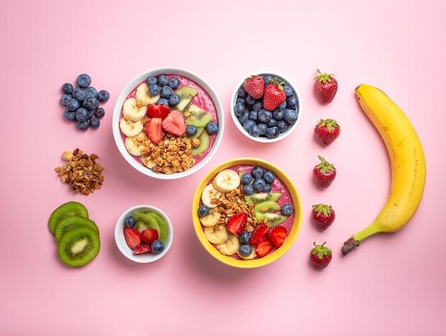 Приготовление миски смузи асаи. ингредиенты для приготовления свежей миски для смузи: свежая клубника, банан, черника, киви и мюсли на пастельно-розовом фоне. крупный план, вид сверху, здоровое питание