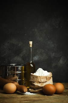 料理とベーキングの背景。生地とベーキングパン、パスタ、ピザの製品や食材を使用した古いキッチン