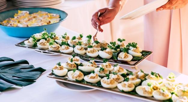 Приготовление и украшение яиц для кейтеринга на вечеринке, например, на свадьбе или мероприятии.