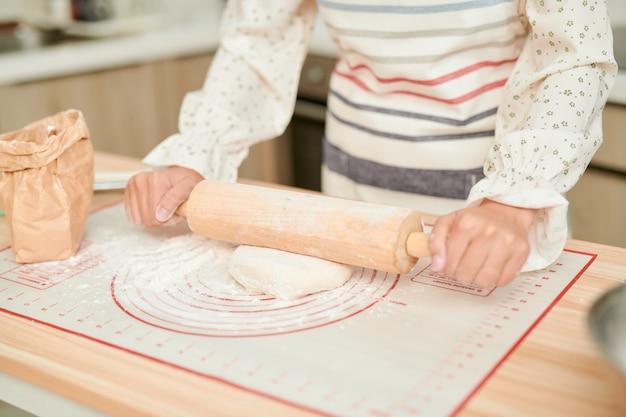 料理と家庭のコンセプト-めん棒で働く女性のクローズアップ