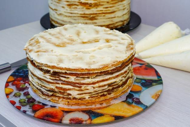 축제 다층 생일 케이크 요리 및 레벨링. 스콘에는 휘핑 크림이 묻어 있습니다. 쿡-제과.