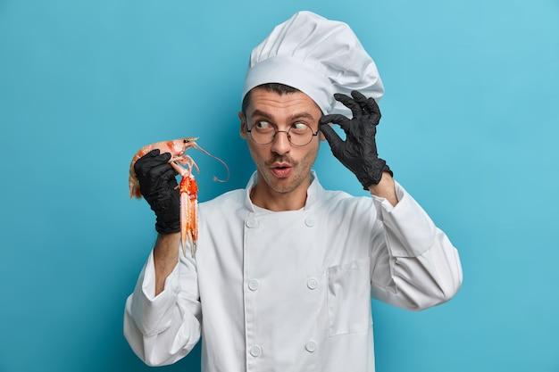 料理とシーフードのコンセプト。プロのシェフが未調理のロブスターやザリガニを持ち、特別な日のためにベジタリアン料理を準備し、白い制服を着ています