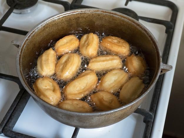 Cooking arabic sweets celebration eid ramadan. traditional turkish dessert tulumba - tulumba tatlisi.