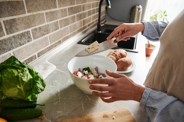 집에서 요리하기. 집에서 부엌에서 채식주의 샐러드를 준비하는 확대 사진.