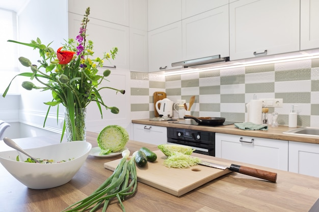 Готовим в домашних условиях, овощи для салата, капуста, огурец, зеленый лук на разделочной доске с ножом, интерьер космической кухонной мебели, приготовление еды на плите, букет цветов