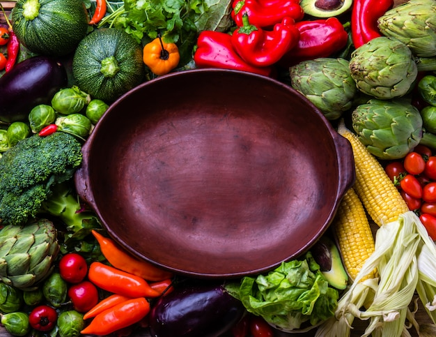 Cooking autumn harvest background concept. fresh organic vegetables around empty clay pot