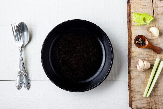 Cooking background concept. empty rustic black cast iron plate, spice and cutlery over wooden background.