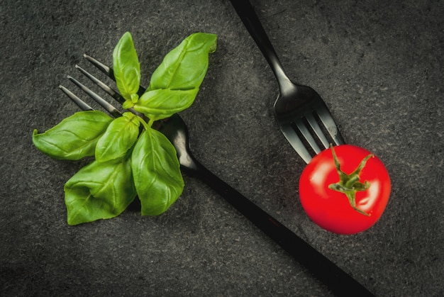 料理の背景。新鮮な野菜と葉野菜のサラダの概念。黒カトラリーフォーク、サラダのバジルルッコラトマトドレッシングとスプーンナイフのセット。黒い石のテーブルの上。トップビューcopyspace