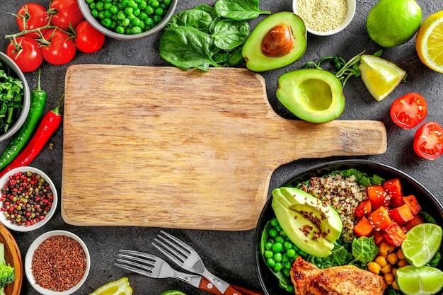 커팅 보드와 함께 요리 배경 프레임입니다. 건강한 음식. 퀴노아, 아보카도, 야채, 조미료, 감귤류, 신선한 허브.