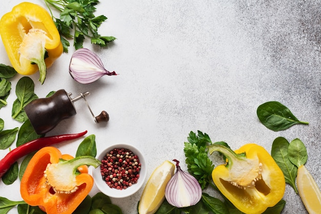 Cooking background. fresh ingredients for eating vegetables, spices, herbs and olive oil gray concrete old background. top view.