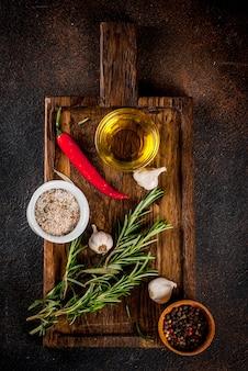 Приготовление фона, травы, соль, специи, оливковое масло на разделочной доске