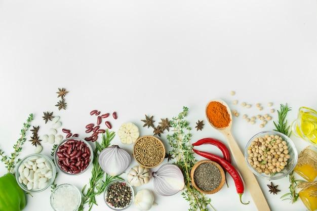 料理の背景、ハーブ、塩、スパイス、オリーブオイル、白い背景のコピースペース。上からの眺め。新鮮な野菜と食材を使ったヘルシーな料理のコンセプト。テーブルの背景メニュー。
