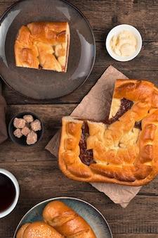 Приготовление фона с яблочным пирогом на коричневой деревянной предпосылке.
